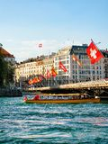 Excursion ferry at Mont Blanc bridge over Geneva Lake. Geneva, Switzerland - August 30, 2016: Excursion ferry at Mont Blanc bridge with Swiss flags over Geneva Stock Images
