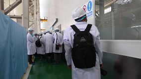 An excursion, people go through the factory workshop, where make transformers. An excursion to the factory 4 march 18 in Shanghai, people in White robes go stock footage