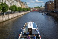Excursion ship is passing under the bridge along the Fontanka River. RUSSIA, SAINT-PETERSBURG, 30 MAY 2018: Excursion ship is passing under the bridge along the royalty free stock photo