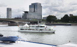 Excursion ship Rheinland. Cologne, Germany - August 20, 2016: Excursion ship Rheinland driving on River Rhine nearby Deutzer Bruecke in Cologne, Germany. Some Royalty Free Stock Photos
