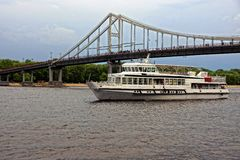 Excursion ship swims to down the river near a bridge. White ship on the river and foot-bridge on a background sky stock photo