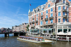 Excursion ship with tourists in Amsterdam canal Royalty Free Stock Photography