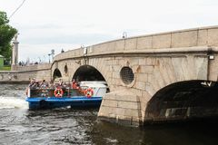 Excursion ship under the bridge. Details and elements of the architecture of the historic center of St. Petersburg royalty free stock images