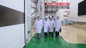 An excursion to the factory, people in White robes go through the factory workshop, which makes transformers. For lowering energy. A group of students. Energy stock footage