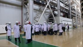 An excursion to the factory, people in White robes go through the factory workshop, which makes transformers. For lowering energy. A group of students. Energy stock video