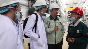 An excursion to the factory, people in White robes go through the factory workshop, which makes transformers. For lowering energy. A group of students. Energy stock video footage
