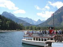 Excursion vessel on Waterton Lakes discharges visitors. Excursion boat on Waterton Lakes, Alberta ties to dock to allow a brief walk by tourists to the USA stock image