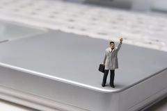 Excuse me, I need some help here!. Businessman Figurine on laptop royalty free stock image