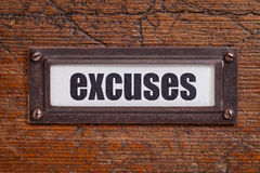 Excuses - file cabinet label. Excuses  - file cabinet label, bronze holder against grunge and scratched wood Royalty Free Stock Photos