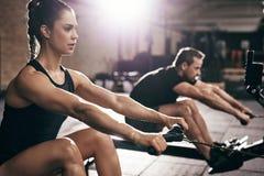 execising在称举的机器的健身房的人们 免版税库存照片