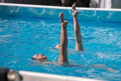 Executando o dueto artístico na piscina: Natação sincronizada durante o exercício imagem de stock royalty free