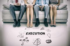 Composite image of execution text surrounded by various web icons. Execution text surrounded by various web icons against portrait of executives waiting for Stock Image