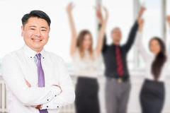 Executive asian boss with his successful business team at background. Multiracial people is a good addition for running a successful business Stock Image