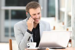 Executive attending phone call in a coffee shop. Executive attending a phone call and using a laptop sitting in a coffee shop Royalty Free Stock Photo
