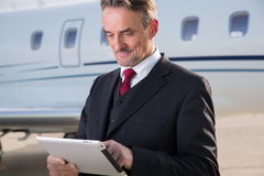 Executive business man in front of corporate jet looking at tabl Stock Photos