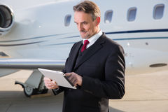 Executive business man in front of corporate jet looking at tabl Royalty Free Stock Photo
