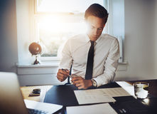 Executive business man working at desk. In a classic office while wearing a suit and tie Royalty Free Stock Photo