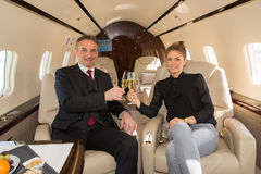 Executive business team in a corporate jet drinking a glass of c Royalty Free Stock Photos