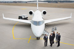 Executive business team in front of corporate jet talking to pil Royalty Free Stock Images