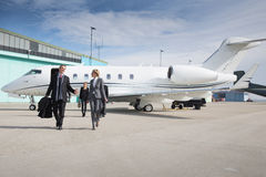 Executive business team leaving corporate jet. Travel stock photography