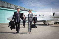Executive business team leaving corporate jet Stock Photo