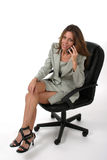 Executive Business Woman with Cellphone 6. Attractive and beautiful executive business woman with very distracting legs sitting in office chair talking on royalty free stock photography
