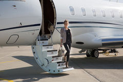 A executive business woman leaving a plane. At the airport Royalty Free Stock Photography