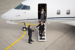 A executive business woman leaving a plane. A executive business women leaving a plane handshake with pilot top view Royalty Free Stock Photography