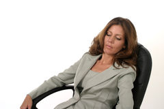 Executive Business Woman Relaxing. Beautiful brunette executive business woman in a business suit relaxing in her office chair royalty free stock photos