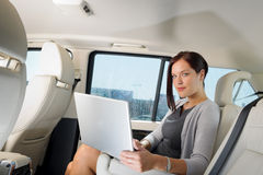 Executive businesswoman work laptop car backseat. Executive woman manager working on laptop sitting car leather backseat Stock Photo