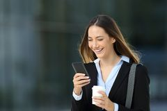 Executive checking content in a smart phone on the street. Single executive checking content in a smart phone and holding a take away coffee walking on the Royalty Free Stock Photo