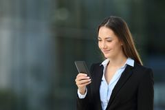 Executive checking a smart phone on the street. Single executive woman checking smart phone messages walking on the street Stock Photography