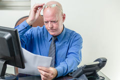Executive comparing computer and written notes Stock Photo