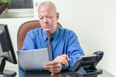 Executive comparing computer and written notes. Corporate worker at desk comparing written notes with computer data stock photos