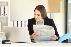 Executive comparing news online with a newspaper. Executive comparing news online in a laptop and a newspaper at office Royalty Free Stock Image
