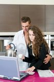 Executive couple kitchen coffee looking lap top Royalty Free Stock Photo