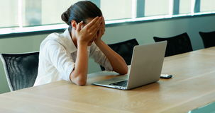 Executive crying while working on laptop in conference room stock video footage