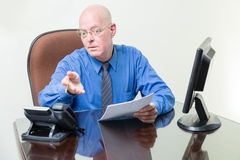 Executive at desk asking question Stock Photo