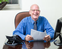 Executive at desk holding papers Stock Image