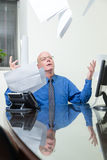 Executive at desk throws papers in air Stock Image