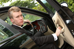 Executive with Drive. Close up of a young executive businessman in a dark pinstripe suit emerging from the driver's side of a saloon car royalty free stock photos