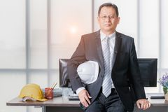 Executive engineer holds white helmet in office stock photography