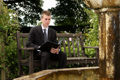 Executive in the Garden. A young executive businessman in a dark pinstripe suit sitting on a garden bench next to a fountain with an open black folder on his lap stock image