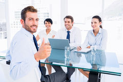 Executive gesturing thumbs up with recruiters during interview Royalty Free Stock Image