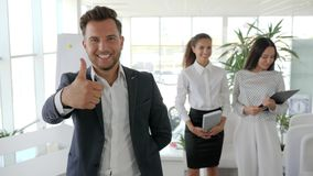 Executive giving thumbs up on background business team in office, positive gesture of boss close-up stock footage