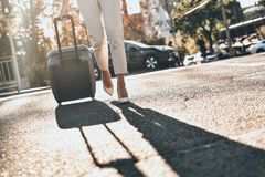 Executive on the go. Close up of young woman pulling luggage while walking outdoors royalty free stock images