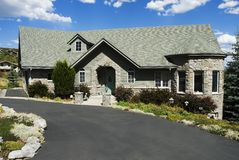 Executive Grey stone home. With landscape on a hill Stock Photos