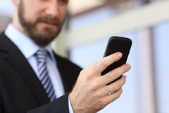 Executive hand using a smartphone in the street. With an office building in the background Royalty Free Stock Photos
