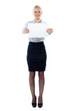 Executive holding a blank billboard. Caucasian female executive holding a blank billboard isolated on white background Royalty Free Stock Photos