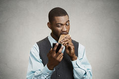 Executive holding smart phone, eating cookie Stock Photo